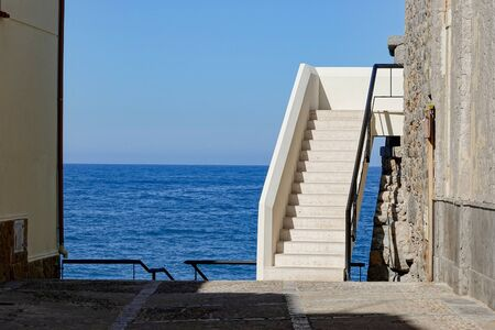 White stairs between building in Southern Europe near the ocean. The entrance to the apartment on a coast at vacation or holiday. Banque d'images - 143534095