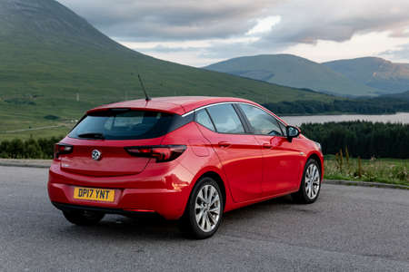 SCOTLAND HIGHLANDS - AUGUST 2, 2019: Red Vauxhall Astra hatchback parked in Scottish Highlands with a view at cloudy landscape when travelling across Scotland.