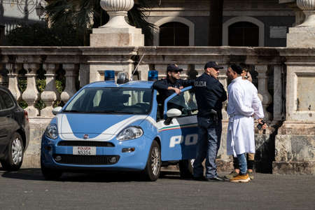 CATANIA, SICILY - FEBRUARY 13, 2020: Fiat Grande Punto estate car of the Sicilian police (Polizia) in Catanie with policemen talking to people in white cloaks. They are used for Saint Agatha Festival