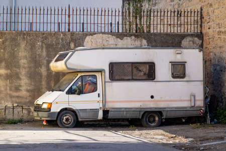 PALERMO, SICILY - FEBRUARY 8, 2020: The old abandond Ford Transit RV vehicle in the streets of Palermo. The wreck of a caravan is no longer used for travelling and may serve to homeless people.