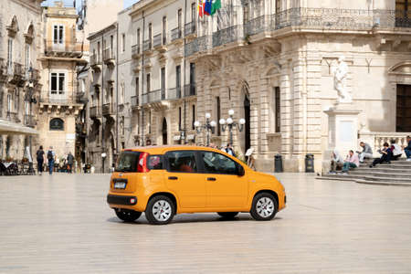 SIRACUSA, SICILY - FEBRUARY 13, 2020: Bright orange Fiat Panda car driving on a Piazza Duomo town square a the center of Siracusa city. It was taken with slight motion blur effect. Redakční