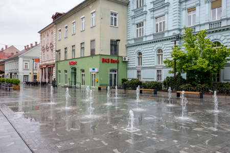 CELJE, SLOVENIA - APRIL 21, 2014: BKS Bank office in the Krekov trg town square in the middle of Celje city, Slovenia with fountain in rainy weather