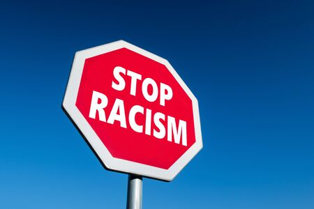 Stop sign with STOP RACISM text in perspective view against blue sky as a reaction for violent activities