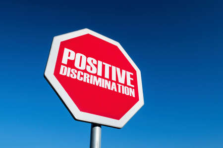 Stop sign as a symbol of overusing the positive discrimination in society as a rising issue of anti-racism fight