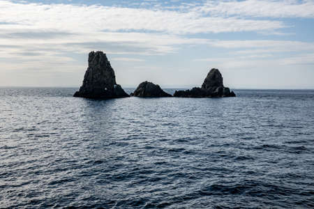 The cliffs of Cyclops (Faraglioni dei Ciclopi) in the sea near Aci Trezza town, Sicily, Italy. Large stones are believed to be thrown at Odysseus