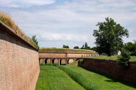 The bridge, red bricks wall and a ditch outside the former Terezin concentration camp, Czech Republic in sunny day 新聞圖片