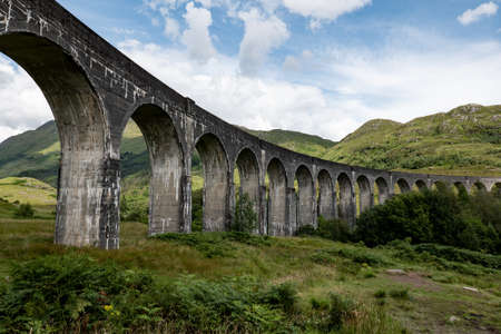 The Scottish landscape with famous Glenfinnan Viaduct in Scotland from bottom with the blue sky and clouds