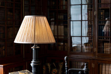 Vintage lamp on a desk in a historical library with a cabinet and reflection in glass