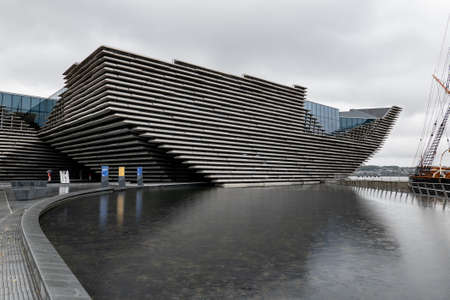 DUNDEE, SCOTLAND - AUGUST 11, 2019: Ship-shaped building of V&A Design Museum in Dundee, Scotland with a water pool in front of it