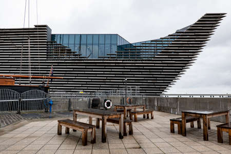 DUNDEE, SCOTLAND - AUGUST 11, 2019: Bench with a table for relax in front of ship-shaped building of V and A Design Museum in Dundee, Scotland