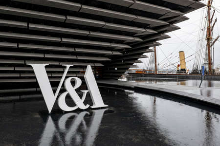 DUNDEE, SCOTLAND - AUGUST 11, 2019: The logo of V and A Art Design Museum in Dundee, Scotland with a water pool in front of it