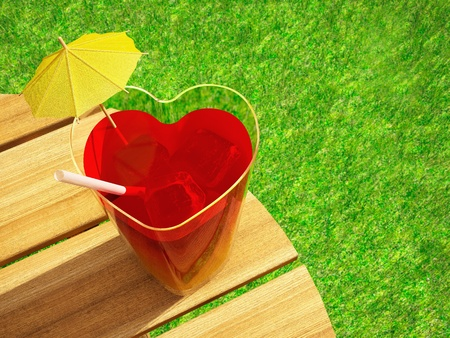 Cocktail in the form of the heart, standing on a wooden table against a green grass
