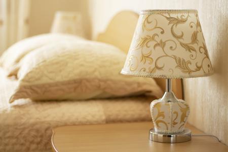 Lampe zum Lesen auf einem Nachttisch vor dem Hintergrund eines gemütlichen Interieurs des Schlafzimmers. Selektiver Fokus. Standard-Bild