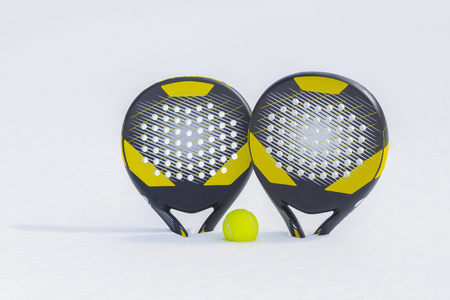 The ball and two beach tennis rackets are thrust in a snow snowdrift.