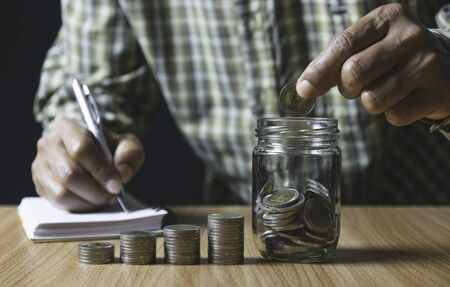 Men are Saint documents about save money and put coin in glass jar on desk.