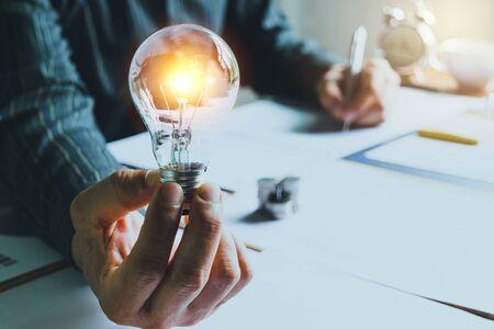 Geschäftsmann, der eine Glühbirne auf dem Schreibtisch im Büro hält und mit Münzen oder Geld auf dem Schreibtisch auf Papier schreibt, auch für Idee, Energie, Energiekonzept.