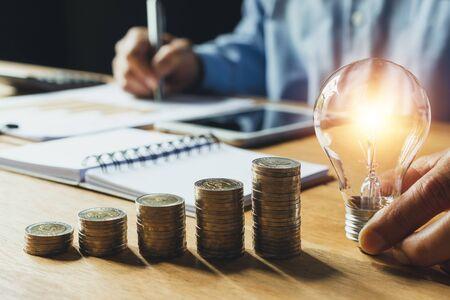 Uomo d'affari che tiene la lampadina sulla scrivania in ufficio e scrive sul taccuino per concetto finanziario, contabile, energetico, idea.