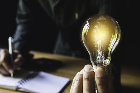 Business man holding light bulb on the desk in office and using computer in financial,accounting,energy,idea concept