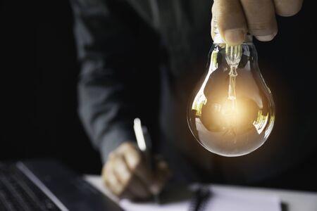 Geschäftsfrau, die Glühbirne auf dem Schreibtisch im Büro hält und Computer im Finanz-, Rechnungswesen-, Energie-, Ideenkonzept verwendet.