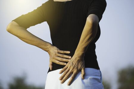 Closeup hands of woman touching her back pain in healthy concept on nature background.