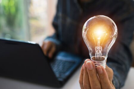 Business woman holding light bulb on the desk in office and using  computer in  financial,accounting,energy,idea concept.