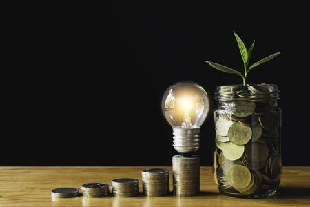 Coins and light bulb put on the table for saving money,energy concept in dark background.