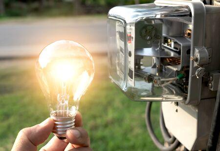 Hand der Person, die Glühbirne von außen mit Wattstundenzähler daneben hält.