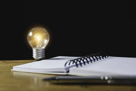 Closeup light bulb on the desk with notebook in office and in financial,accounting,energy,idea concept
