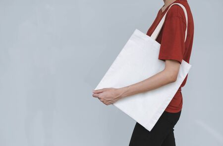 woman carry bag on gray background in save earth concept or say no plastic bag. Stock Photo
