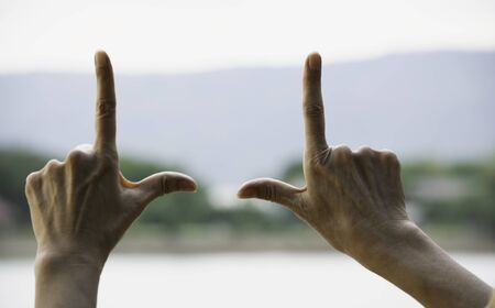 Hands of person making frame distance or symbol in nature.