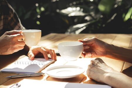 The people holding coffee cup on wooden table in garden with working. Stockfoto