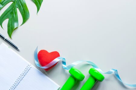 Healthy object on table with dumbbells,notebook a pen,ribbon,leaves of tree and red heart for sport or exercise concept.