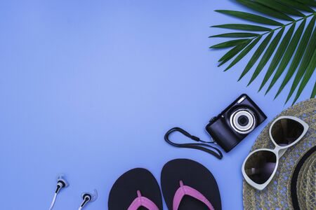 Flat lay, top view with hat,slippers,camera, sunglasses,earphone and green leaf tropical palm for travel,summer and holiday concept on soft blue background.