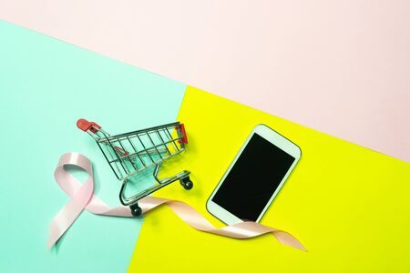 Top view,flat lay smartphone shopping cart with pink ribbon to decoration for shopping and e-commerce concept on pastel colorful background.