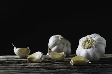Closeup garlic on wooden texture on for cooking on dark background