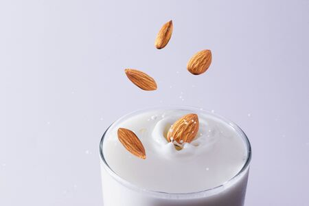 Closeup milk splash with almonds nut  on white background.