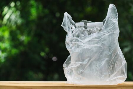 Plastic bottle in plastic bag on wooden in nature background. global warming concept.