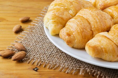 Closeup croissant with almond on wooden table. breakfast concept. 写真素材