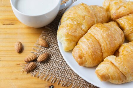Closeup croissant with almond and milk on wooden table. breakfast concept.