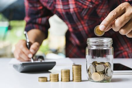 Men are Saint documents about save money and put coin in glass jar also have  calculator, coins on desk  写真素材