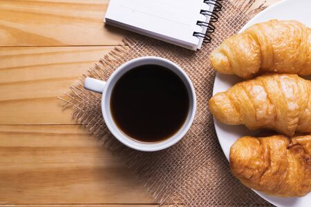 Closeup croissant with coffee on wooden table. breakfast concept.