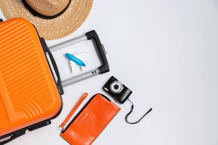 Flat lay orange suitcase with traveler accessories on white background. travel, summer and holiday concept