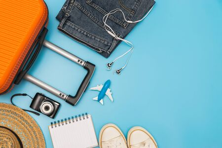 Flat lay orange suitcase with traveler accessories on soft blue background. travel, summer and holiday concept