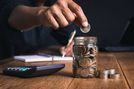 Men are Saint documents about save money and put coin in glass jar on desk on black background.