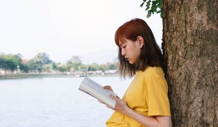 Young girl holding a book for read outdoor in nature background. 写真素材