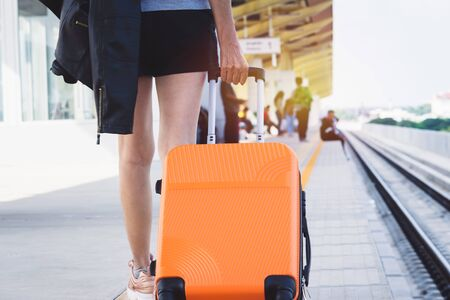 Woman tourist with orange suitcase waiting the train at train station background. travel, tourist, vacation concept.