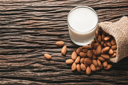 Closeup almonds and milk on wooden texture on dark background. 写真素材