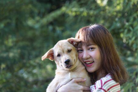 Abrazo de la muchacha del retrato con su perrito en el fondo de la naturaleza.
