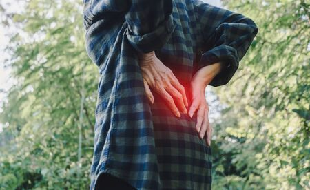 Closeup hands of woman touching her back pain in healthy concept on nature background. Stock fotó
