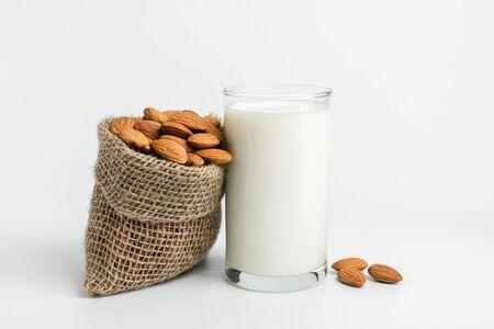 Milk with almonds nut on white background. 写真素材